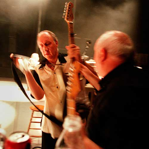 Pete Townshend exchanges guitars with his guitar tech Alan Rogan during The Who's performance at Cynthia Woods Mitchell Pavillion in The Woodlands, TX on August, 29, 2000.